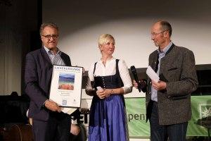 """Dr. Stefan Guggenbichler mit der Urkunde für den Nachwuchspreis für """"The Fire within"""" von Alexej Funke."""
