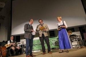 """Manfred Pfeiler (Mitte) vom E-Werk Tegernsee gibt den Gewinner in der Kategorie Lebensraum Berg """"Die Wildheuer - Senkrecht über dem Urnersee"""" von Beat Bieri"""