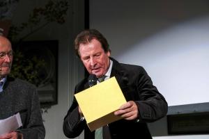 Herbert Doll, monte mare Betriebsgesellschaft, gibt den Gewinner des Kleinen Preises des Bergfilm-Festivals  bekannt, gesponsert durch monte mare: Viacruxis von Ignasi López